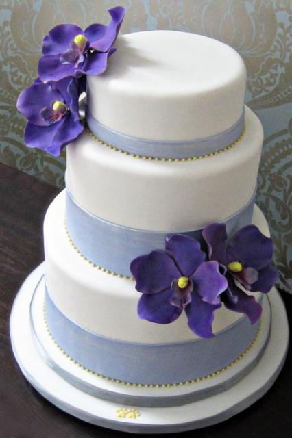 Triple tier round white wedding cake with purple flowers blue bands ...