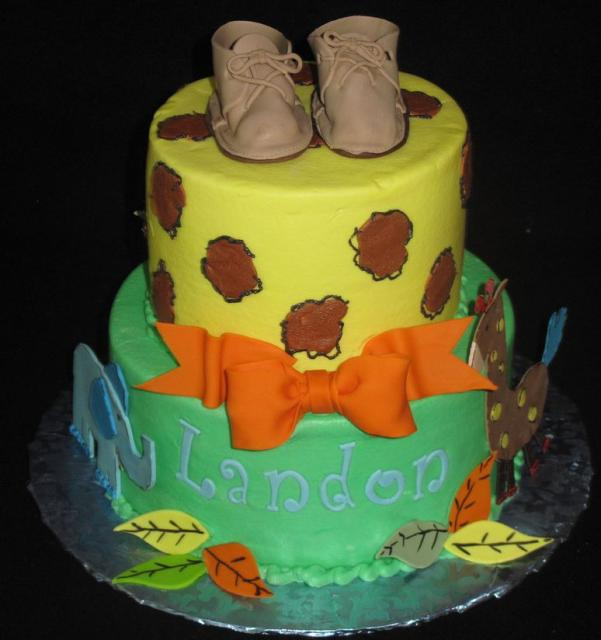 jungle theme baby shower cake for boy with small toddler shoes on top
