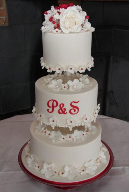 3 tier white round wedding cake with white flowers and red script monogram on middle tier jpg