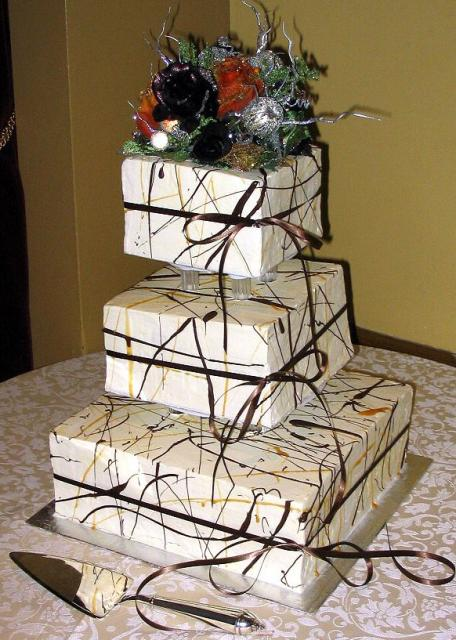Three tier wedding cake with chocolate and ribbons.JPG