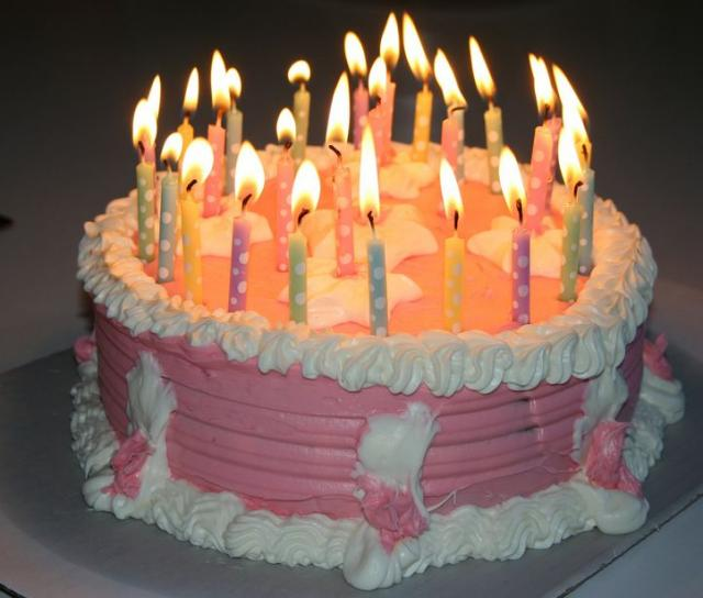 Pink birthday cake with white cream and lots of candles.JPG