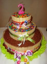 Candy theme three tier second birthday cake with candies surrounding candy layers.JPG