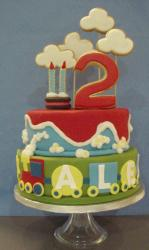 Two tier second birthday cake with trains and clouds and the number two on top.JPG