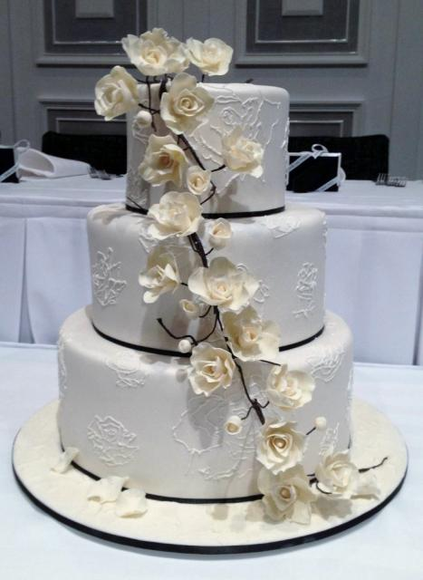3 tier round white wedding cake with floral patterns and white roses.JPG