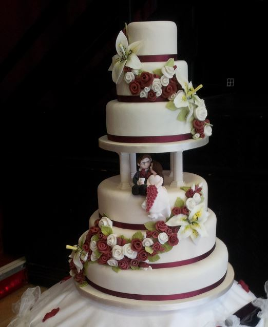 6 tier round white wedding cake with Roman pillers plus bride and groom toppers and roses.JPG