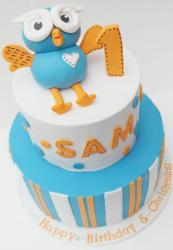 Two tier first birthday cake with baby owl on top.JPG