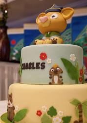 2 tier safari theme cake with baby animal on top.JPG