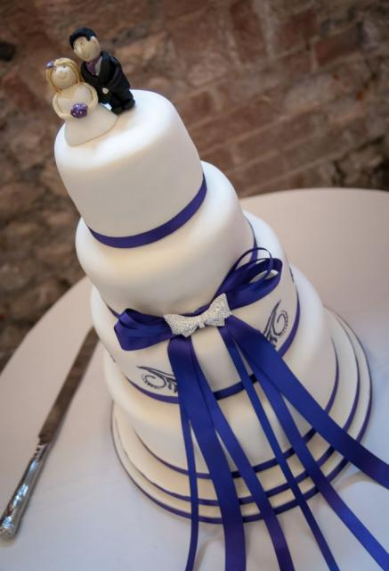 4 tier white round wedding cake with purple bow and bands with bride and groom topper.JPG