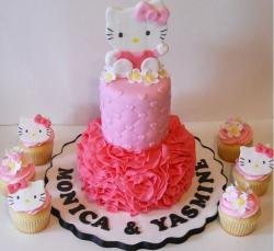 2 tier Hello Kitty pink cake with accompanying cupcakes.JPG