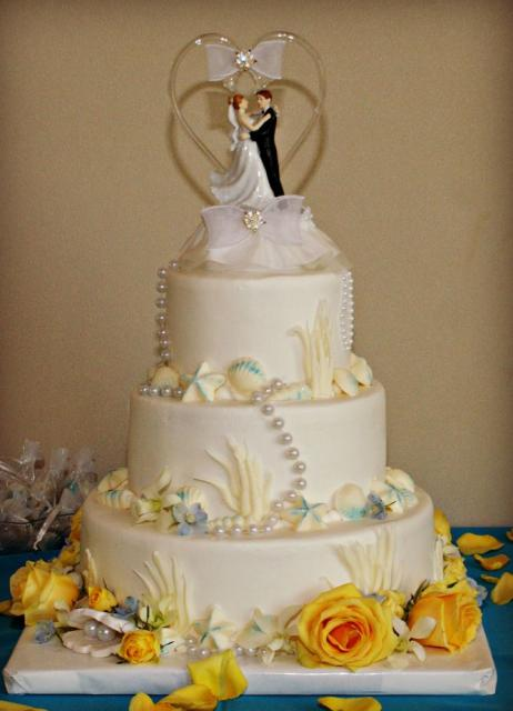 3 tier round white ocean theme wedding cake with shells and yellow rose petals plus husband wife topper.JPG