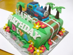 Fancy kids birthday cake with Thomas the train running on the train track.PNG