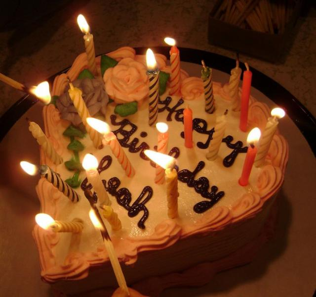 Heart shaped cream birthday cake with lit candles.JPG