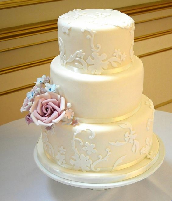 Ivory 3 tier wedding cake with pink rose on second tier.JPG
