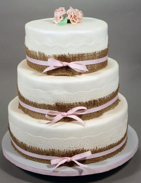 3 Tier Round White Wedding Cake With Pink Bands Holding Straw Fence With Pink Roses On TopJPG