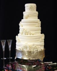 Ivory 5 tier round wedding cake with white floral decor and drape-like layers.JPG
