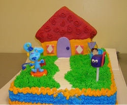 Colorful kids birthday cake with blue clues house.PNG