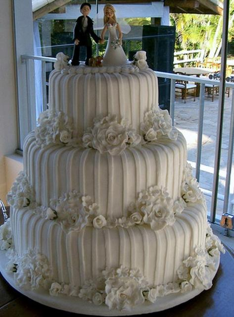 Ivory 3 tier wedding round cake with vertical white stripes white flowers and bride groom and pet toppers.JPG
