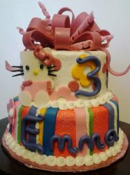 Two tier Hello Kitty 3rd birthday cake with pink bow on top.JPG