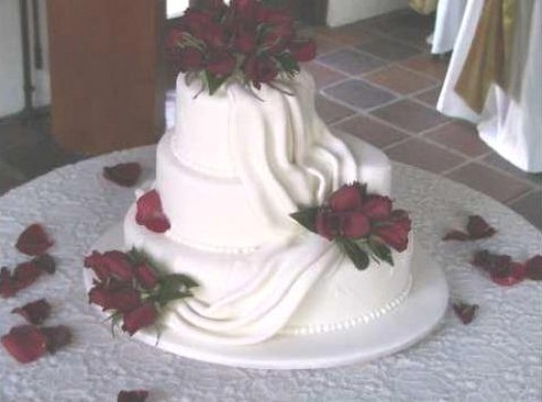 wedding cakes in white with red dark roses looking very romantic cake