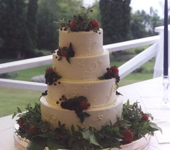 wedding cakes in four tier with red dark color roses and full of green leaves