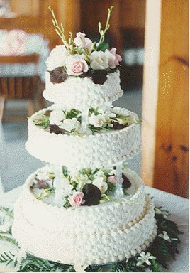 close picture of wedding cakes with traditional patterns with fresh flowers and floral topper