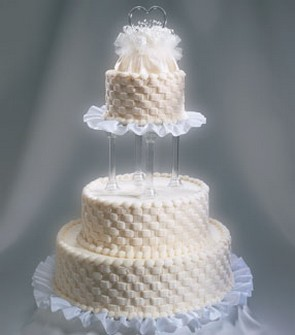 picture of wedding cakes in three tier in creamy color with cool patterns with floral topper