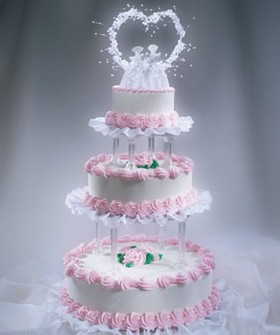 Traditional wedding cakes with light pink decor and white bride and