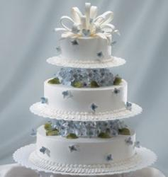 White wedding cake in three tiers with blue flowers, green and cream floral topper