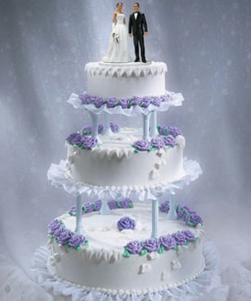 Three tier wedding cake in white and purple flowers and bride and ...