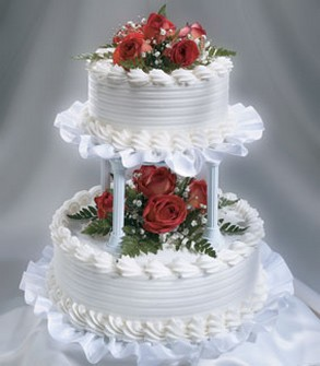Snow White Wedding Cake With Bright Red Flowers And Green