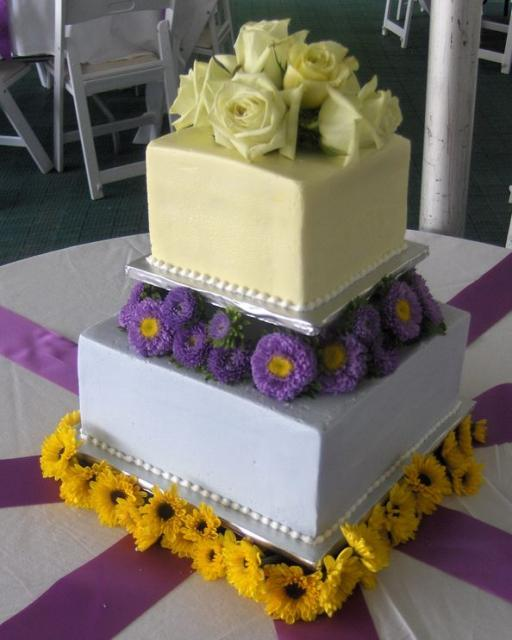 Two tier square wedding cake with carnations and ...