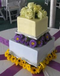 Two tier square wedding cake with carnations and sunflowers.JPG