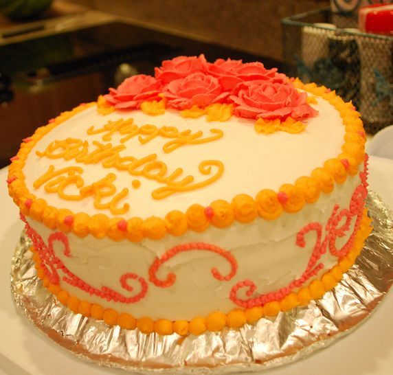 Photograph of White birthday cake w/ orange cream + red rose petals