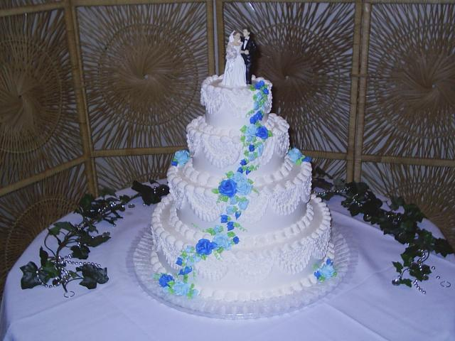 Wedding Cakes in four tier with blue flowers and groom and bride topper