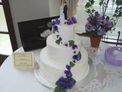 Photo of beautiful Wedding Cakes in white with dark purple flowers
