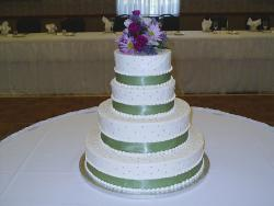 Wedding Cakes in four tier with green ribbons and purple flowers topper