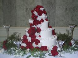 Four white Wedding Cakes with lots of bright red flowers