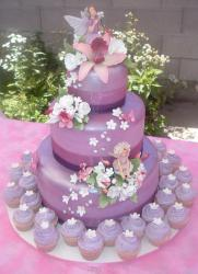 Three tier lavender cake with matching cupcakes surrounding.JPG