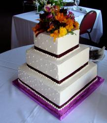 Three tier square white wedding cake with fresh flowers on top.JPG