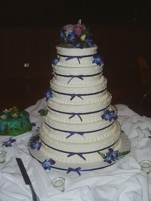Six tier Wedding Cakes with dark blue and purple floral toper and dark ribbons