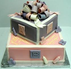 Two tier baby shower cake in play blocks theme with ribbon and baby bottles.JPG