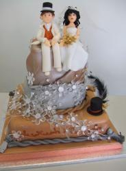 Toffee and chocolate three tier wedding cake with large detailed bride and groom toppers.JPG