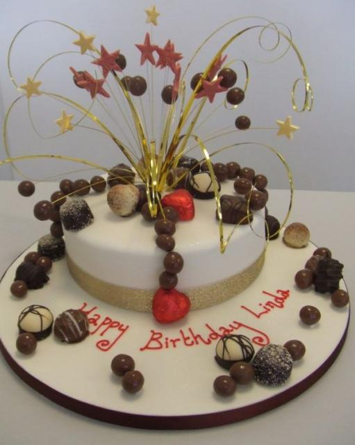 Image of circular white birthday cake w/ chocolate treats