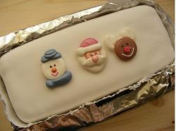 Simple white Christmas cake with Santa faces.JPG