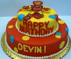 Two tier cartoon robot theme birthday cake in orange and yellow.JPG