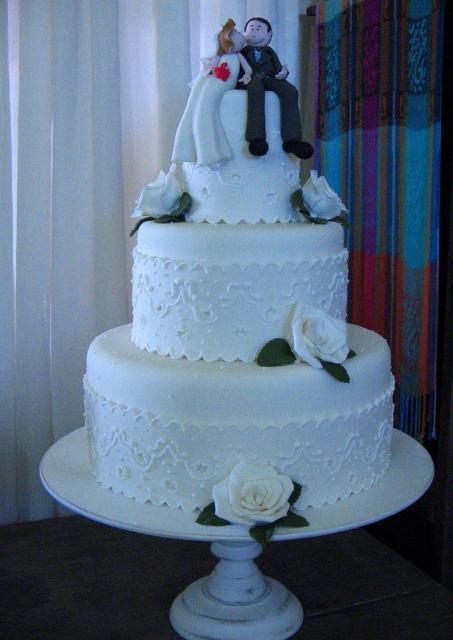 Tri-tier round wedding white cake with detailed bride ...