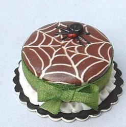 Chocolate halloween spider web cake with spider on top and green ribbon.JPG