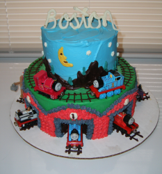 Two tiers Thomas the train cake with trains cake toppers picture.PNG