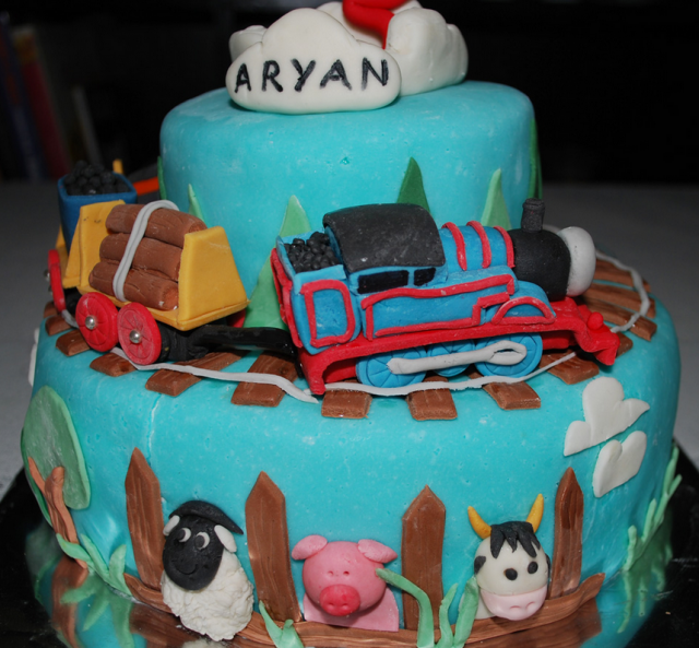Blue Thomas train on train track passing the farm animals_perfect Thomas the train birthday cake for children.PNG