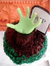 Halloween RIP cake with a green hand stick up from the ground.JPG